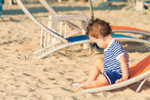 Toddler dressed as a sailor sitting on a tilted sunbed and explo — Stock Photo