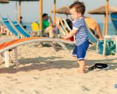 Toddler dressed as a sailor standing on a beach and playing with — Stock Photo