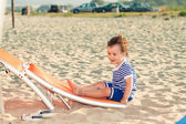Playful toddler dressed as a sailor sitting on a tilted sunbed o — Stock Photo