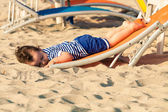 Sweet toddler dressed as a sailor lying from a top of a sunbed o — Stock Photo