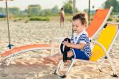 Sweet toddler dressed as a sailor sitting on a beach chair near — Stock Photo