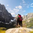 Young tourist couple standing  on stone near mountain lake — Stock Photo #59390431
