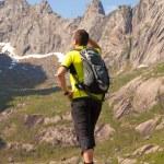 Young tourist man is standing on stone near mountain lake — Stock Photo #59390477
