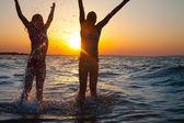 Två glada unga tjejer hoppar på stranden — Stockfoto