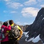 Young tourist couple standing  on stone near mountain lake — Stock Photo #65226061
