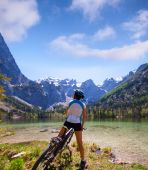 Young woman riding a bike beside Alpine lake — Stok fotoğraf