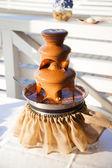 Festive dessert - chocolate fountain. Fondue Chocolate. — Stock Photo