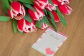 Тюльпаны и лист для заметок на фоне деревянной поверхности — Стоковое фото