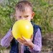 Small boy blowing up a colorful yellow balloon — Stock Photo #58316115