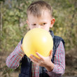 Small boy blowing up a colorful yellow balloon — Stock Photo #58316143