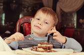 Contented little boy eating cake for dessert — Stock Photo