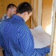 Two carpenters or builders discussing a plan — Stock Photo #59176389