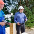Two builders watching something on site — Stock Photo #60217007