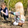 Little boy and girl playing in woods with sticks — Stock Photo #66021189