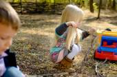 Little Blond Girl Playing Sticks on the Ground — Photo