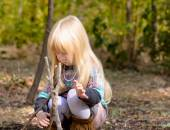 Serious Blond Girl Assembling Sticks on the Ground — 图库照片