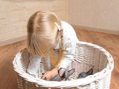 Little girl playing with a basket of kittens — Stock Photo