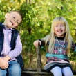 Happy Little Kids Sitting on a Wooden Garden Fence — Stock Photo #66236537