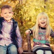 Happy Little Kids Sitting on a Wooden Garden Fence — Stock Photo #66236675