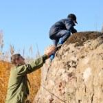 Scout helping a young boy rock climbing — Stock Photo #66236789