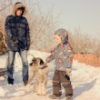 Little boy patting a dog on a lead — Stock Photo #66236915