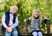 Happy Little Kids Sitting on a Wooden Garden Fence — Stock Photo