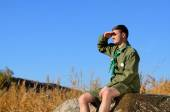 Boy Scout Sitting on Rock Watching Over the Field — Stock Photo
