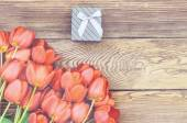 Bouquet of fresh tulips with a gift — Stock Photo