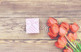 Bouquet of fresh tulips with a gift — Fotografia Stock
