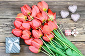 Bouquet of fresh tulips with a gifts — Stock Photo