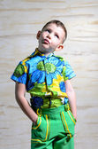 Little boy in colorful clothes standing thinking — Stock Photo