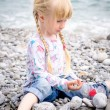 Blond Girl Building Stone Wall on Rocky Beach — Stock Photo #74256219