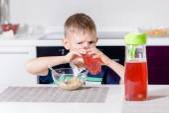 Little boy drinking fruit juice in a kitchen — Stok fotoğraf