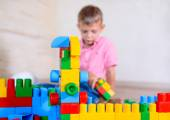 Happy young boy playing with his building blocks — Стоковое фото