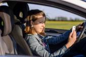Young female driver reading a text message — Stock Photo