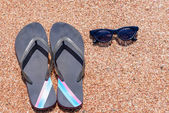 Slip slops sunscreen and sunglasses on a beach — Stock Photo