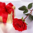 Golden gift box and red roses on white satin background — Stock Photo #71744713
