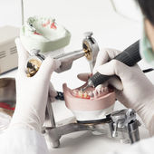 Dental technician working with articulator — Stock Photo