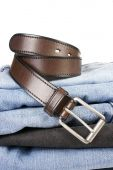 Stack of various shades of blue jeans with brown belts — Stock Photo