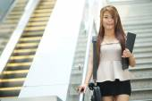 Young business woman walking in front of escalator — Stock Photo
