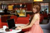 Young business woman sitting in cafe with her laptop. — Stock Photo