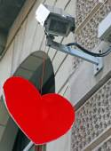 Red heart hanging from a surveillance camera — Stock Photo