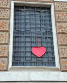 Red heart hanging on the grating outside a building — Stock Photo