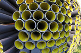 Corrugated pipes in a roadworks for laying optical fiber for tel — Stock Photo
