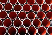 Red corrugated pipes for laying electric cables and optical fibe — Stock Photo
