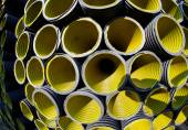 Yellow corrugated pipes in a roadworks for laying optical fiber  — Stock Photo
