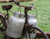 Rusty bike of the milkman with two old milk cans and broken sadd — Stock Photo