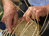 Hands of skilled craftsman make a wicker basket — Stock Photo