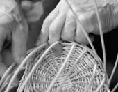 Hands of skilled craftsman create a wicker basket — Stock Photo