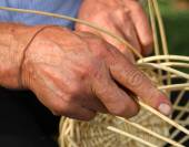 Skilled craftsman who works the cane to create a wicker basket — Stock Photo